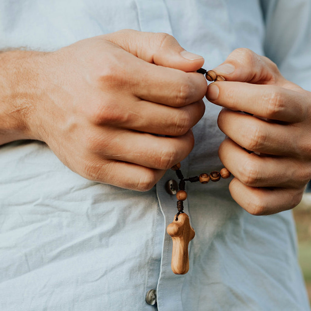 close up of a man's hands praying on the Peace Prayer Chaplet