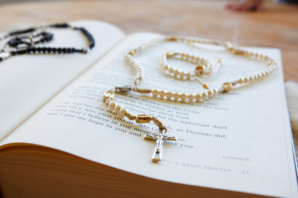 black rosary and white pearl rosary and bracelet set resting on book of Basic Prayers