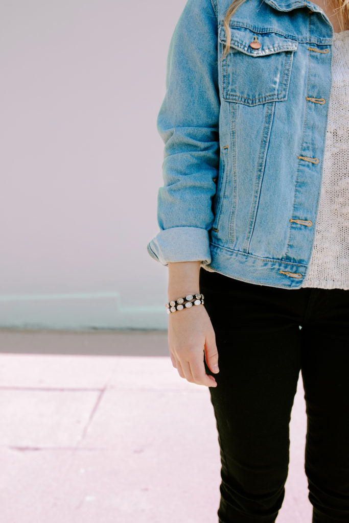 young woman wearing denim jacket and black pants standing against a plain outdoor wall arm at her side wearing blessing bracelets