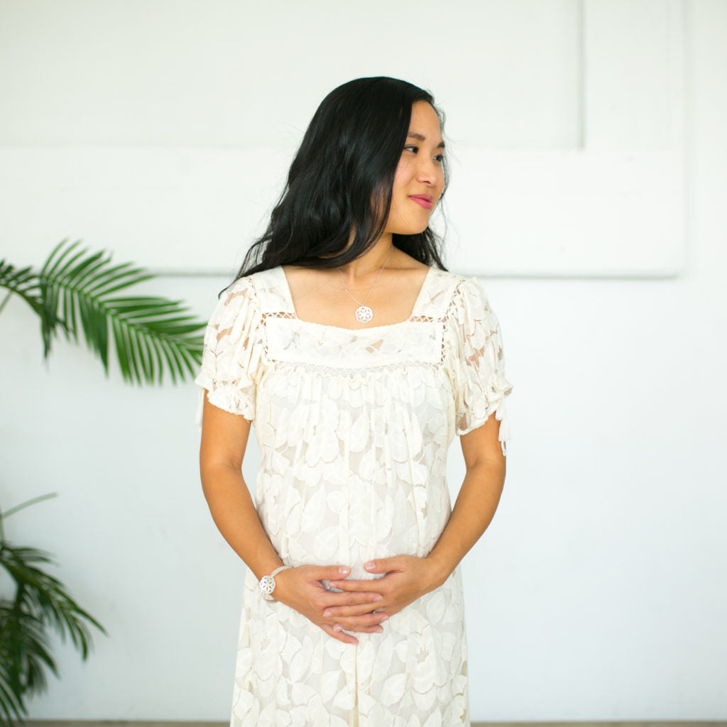 Maria wearing cream lace dress standing with hands clasped of her baby bump