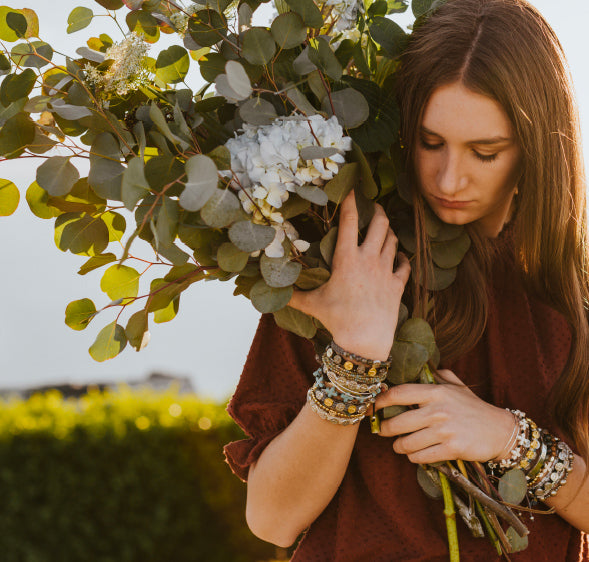 my-saint-my-hero-mission-statement-page-young-woman-wearing-inspirational-handwoven blessing bracelets holding large bouquet flowers magic hour sunset