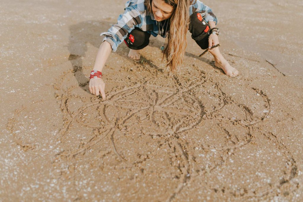 Nia Peeples drawing the Seed of Life in the sand at the Sea of Galilee