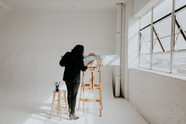 Artist Vivian at work in her studio standing at easel