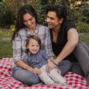 John Stamos and Caitlin Stamos wearing their My Saint My Hero Share the Love St. Amos Collection