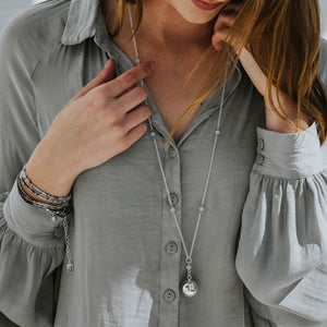 Awaken Angel Chime Necklace in silver or woman in gray blouse