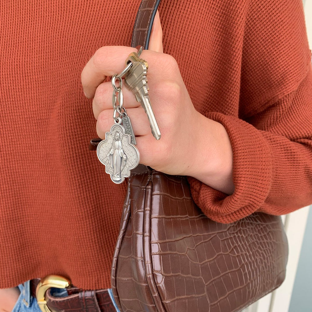 Woman holding Blessed Mother Mary Medal Key Ring with brown purse