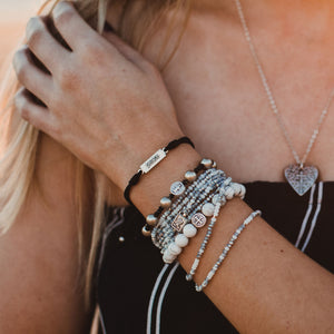Woman wearing stack of Blessing Bracelets featuring the Peace White Howlite Power Blessing Bracelet