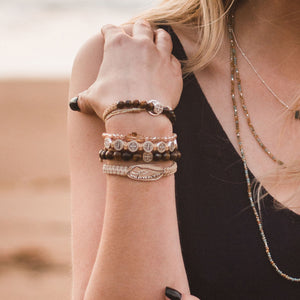 Courage Tiger's Eye Power Bracelet on a blonde woman at the beach