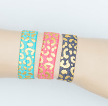 Laden Sie das Bild in den Galerie-Viewer, 3er Set Elastisches Armband + Haargummi mit Leoprint in Gold hell