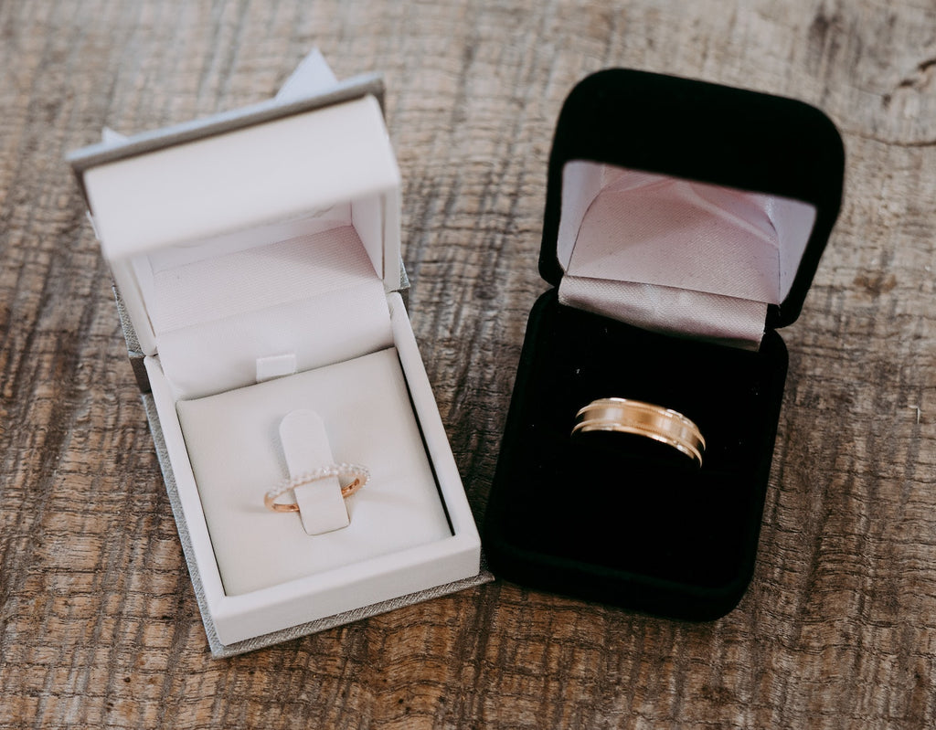 wedding bands in two boxes, one black, one white
