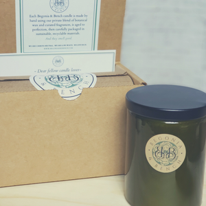 Premium Botanical Wax Candle. Signature Collection Candle in Vintage Green, size Grand with Black Lid next to Brown Kraft Box Packaging with white sticker, cardstock and label against a white brick background, sitting on top light wood.