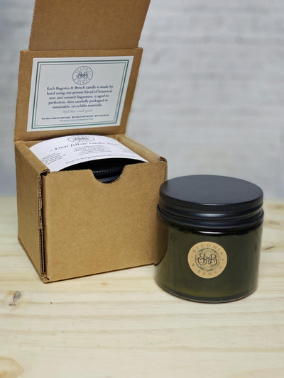 Premium Botanical Wax Candle. Candle in Vintage Green, size Companion with Black Lid next to Brown Kraft Box Packaging with a white sticker and white cardstock against a white brick background, sitting on top of light wood.