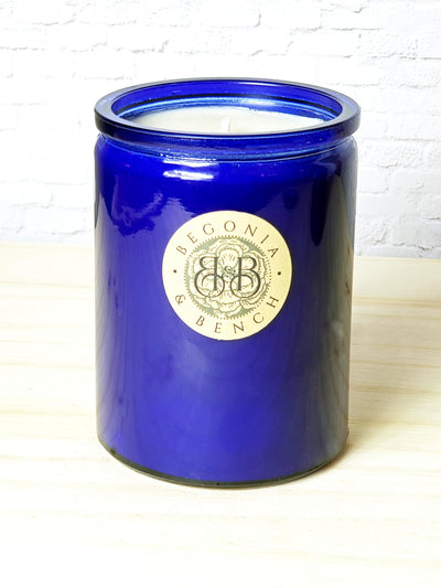 Premium Botanical Wax Candle. Signature Collection Candle in Cobalt Blue- size Grand against a white brick background, sitting on top of light wood.