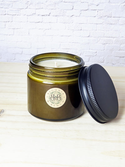 Premium Botanical Wax Candle. Candle in Vintage Green, size Companion with Black Metal Lid laying against Vintage Green jar, against a white brick backdrop, sitting on top of light wood.