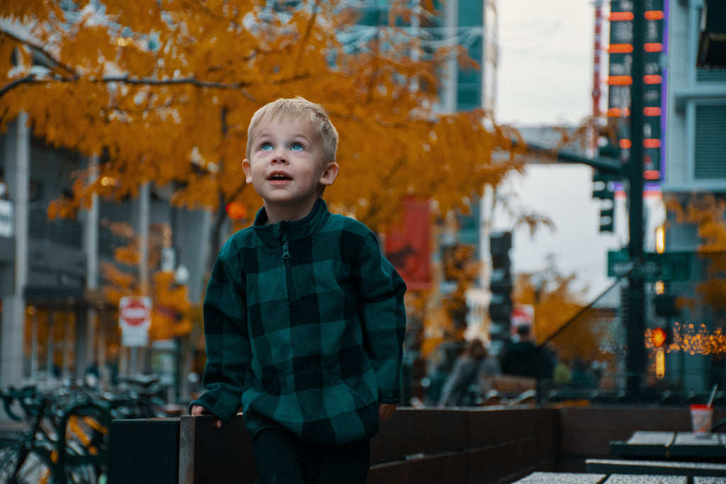handsome blond little boy in town autumn