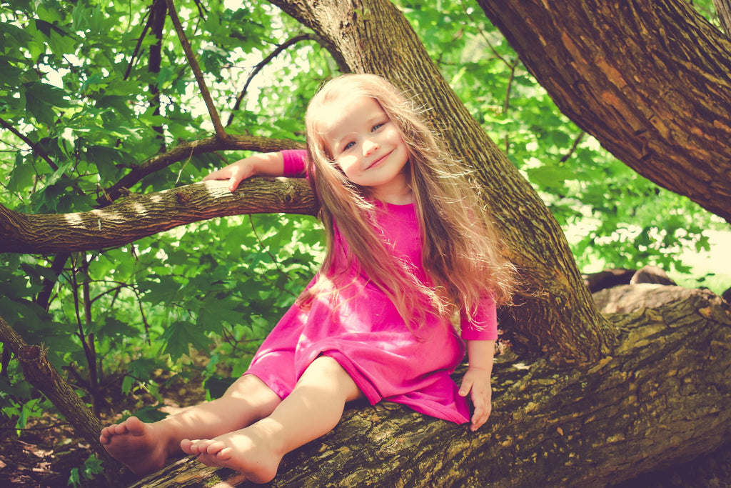 little cute blonde girl in pink dress on a tree