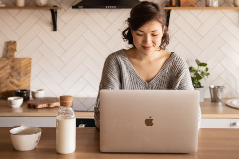 Woman working on MacBook next to bottle of milk