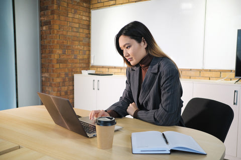 Woman Working on Laptop next to notebook and coffee