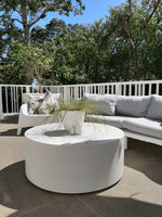 100cm x 40cm high round limestone lightweight concrete coffee table in a patio setting with a white outdoor lounge suite and grey cushions in front of a backdrop of large green trees on a beautiful sunny day