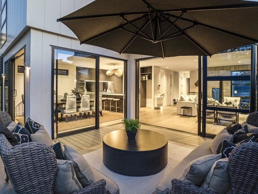 Our 100cm round coffee table displayed on an outdoor patio at night with outdoor wicker furniture looking into an indoor brightly lit kitchen and living area