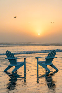A photo of a pair of Adirondack Chairs on the beach at sunrise with sea fog