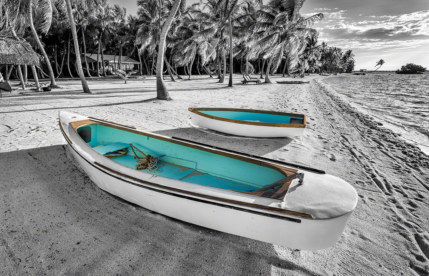 A photo of two turquoise colored boats with the rest of the scene in black and white