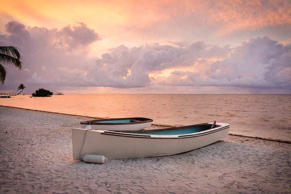 Two rustic boats on a beach at sunrise