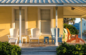 A photo of Adirondack Chairs on the porch of an old Florida home