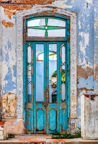 A photo of a turquoise colored rustic door on a home in Havana, Cuba