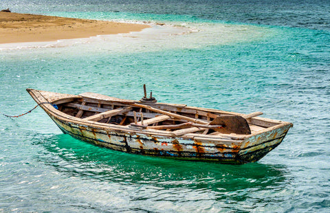 A photo of a rustic Haitian fisherman's boat in beautiful Caribbean water