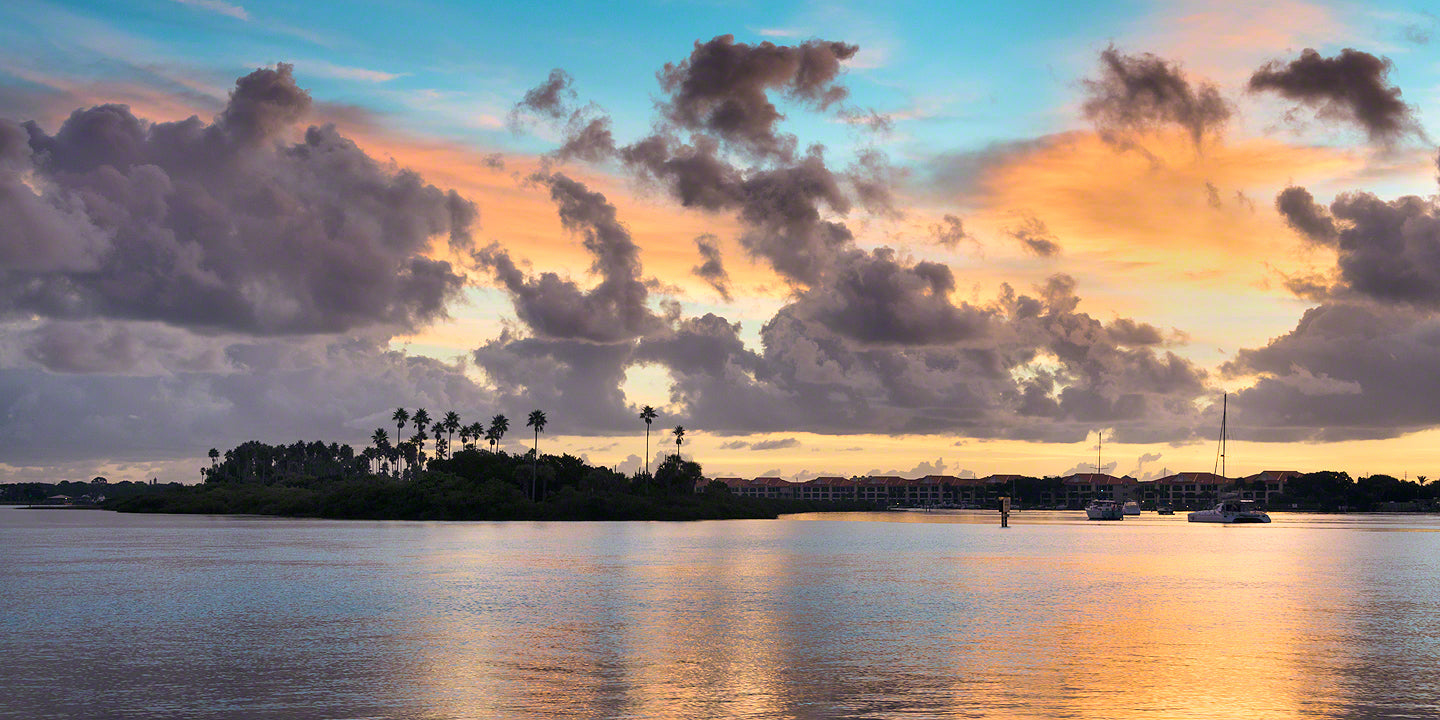 A sunrise view of Chicken Island and sailboats in the Indian River waterway.
