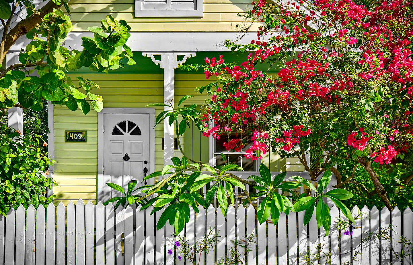A photo of a key lime colored cottage home surrounded by tropical flowering plants in Key West, Florida