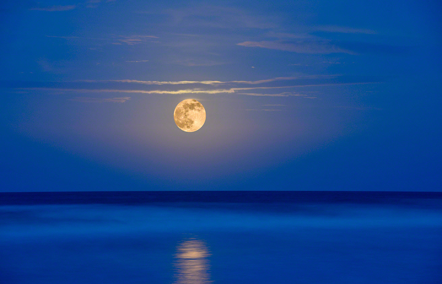 A photo of a super moon rising out of the ocean