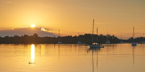 A photo of the sun rising with sailboats on the Indian River