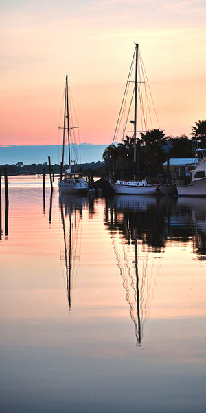 A photo of two sailboats at sunrise in New Smyrna Beach, Florida