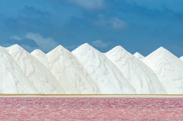 A photo of a pink salt pan and a mountain of salt in Bonaire.
