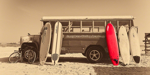 A photo of a bus with surf boards on the beach