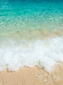 A photo of clear turquoise water crashing onto the beach in the Bahamas