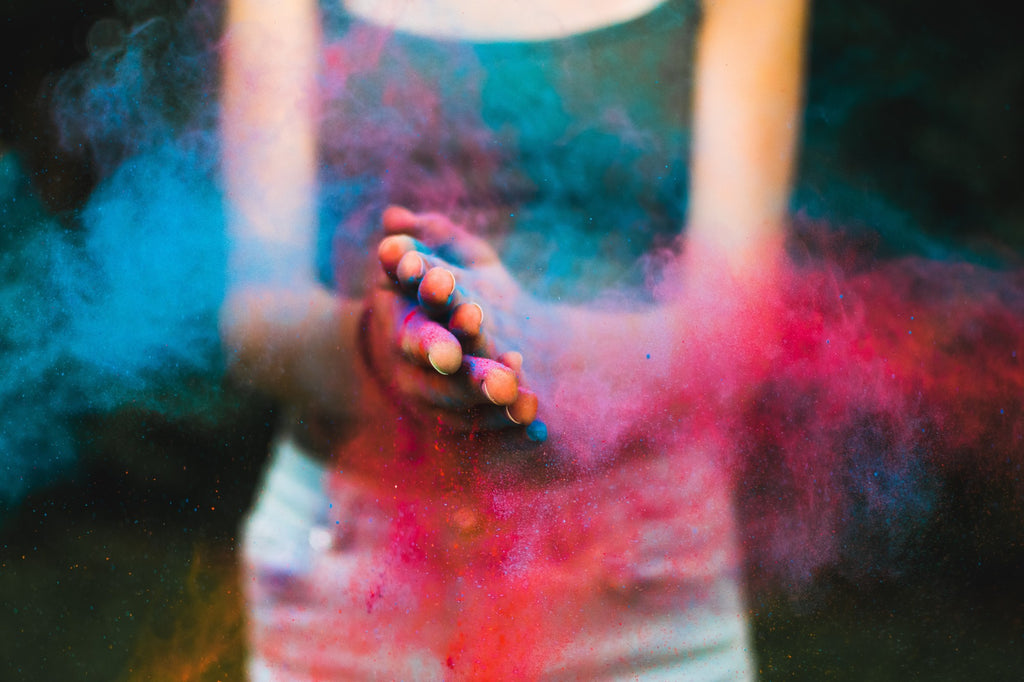 clapping hands with holi color powder
