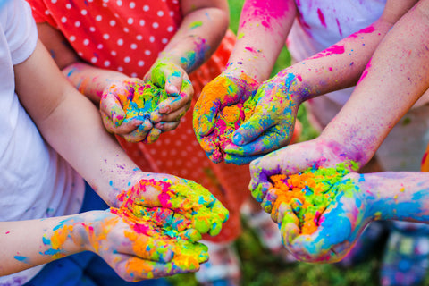 School children holding color powder