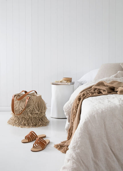 Boho shopper with jute fringes and leather handles next to bed