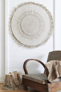 circular jute wall hanging in macramé above wooden sofa