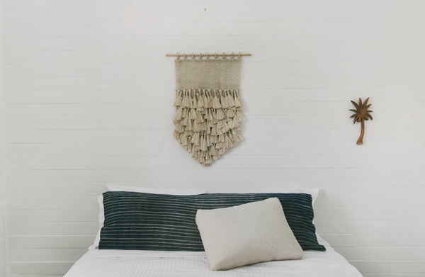 small jute wall hanging on bamboo hanging rod in bedroom above bed head
