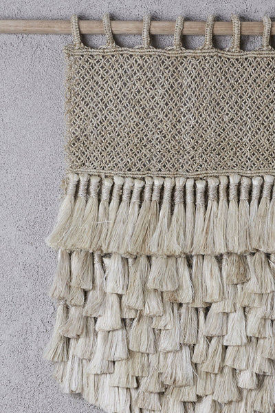detail of jute wall hanging with tassels on bamboo hanging rod