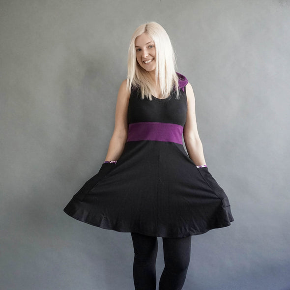 the model is showing the fun flowy circle skirt and patch pockets. Her design is purple and Black and has a collar.