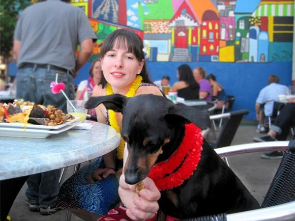 Lady feeding a dog in Double Wide Grill restaurant