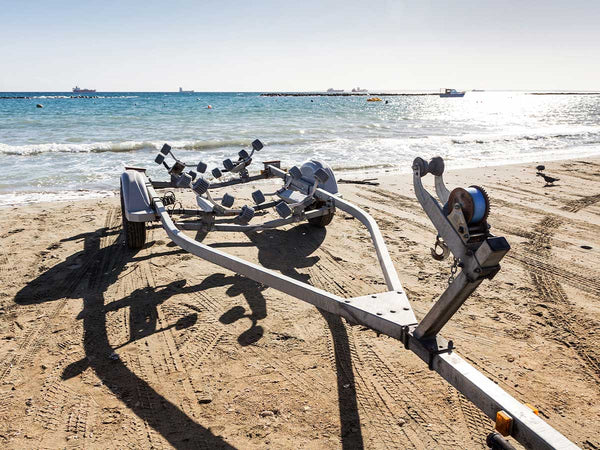 Image of a boat trailer in front on a beach.