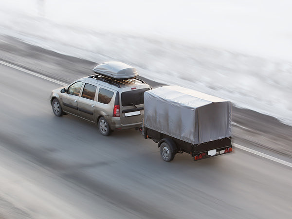 Image of a car driving down the highway with a trailer attached.
