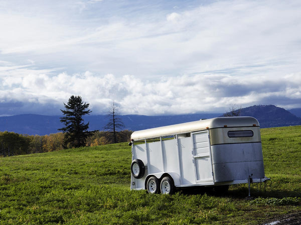 Image of a horse trailer in a field.