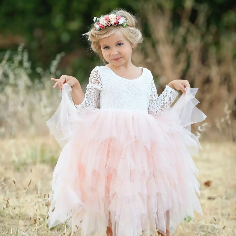 Girl in a meadow wearing a Bohemian style pink party dress and head garland.